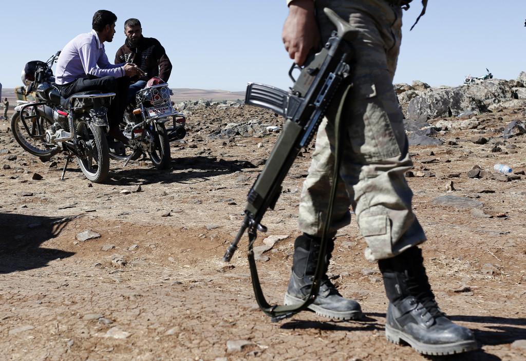 """თურქი ჯარისკაცი მორიგეობს, ამ დროს კი მამაკაცები  თურქეთის ტერიტორიიდან აკვირდებიან ბრძოლების მიმდინარეობას სირიელი ქურთებისა და """"ისლამური სახელმწიფოს"""" (IS) მებრძოლებს შორის ქალაქ კობანის გარეუბანში, სირიაში.  © EPA 21.10.2014"""