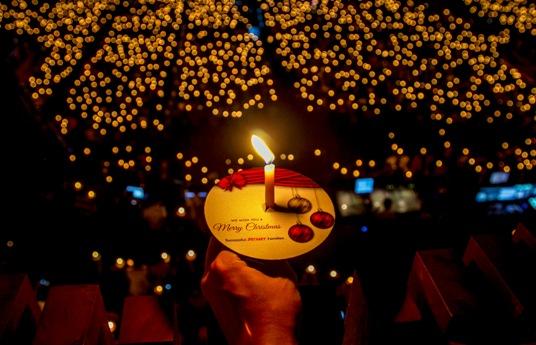 ინდონეზიელ კათოლიკეს უჭირავს სანთელი საშობაო მესაზე. სურაბაია, ინდონეზია