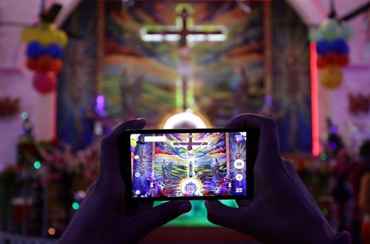 ინდოელი მორწმუნე იღებს ფოტოს წმინდა მარიამის ტაძარში შოის ღამეს. ინდოეთი