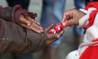 ინდოელი მიუსაფარი ბავშვები არასამთავრობო ორგანიზაციის მიერ ორგანიზებულ შობის დღესასწაულზე.   ფოტო: EPA/RAMINDER PAL SINGH