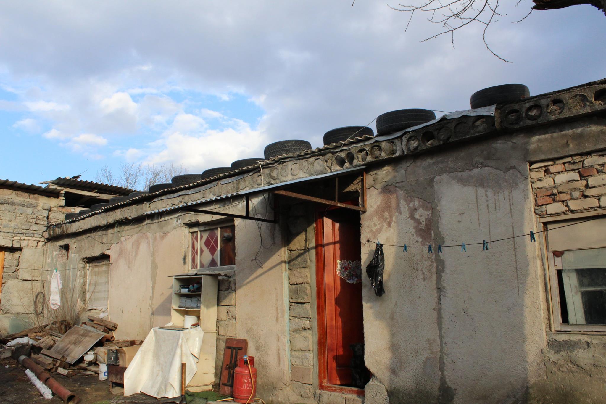 ავტომობილის ბორბლებითა და სხვა სიმძმეებით დამაგრებული სახურავები. ფოტო: გიორგი დიასამიძე/ნეტგაზეთი