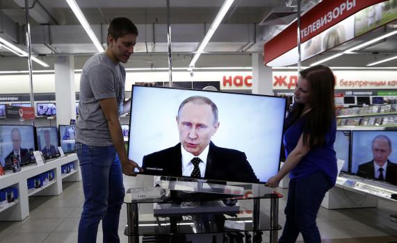 რუსეთის სახელმწიფო ტელევიზიები (TV) და პუტინი © EPA/YURI KOCHETKOV
