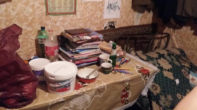 ოთახში არსებული ერთადერთი მაგიდა, რომელზეც დევს ბავშვების წიგნები, სახატავი რვეულები და კონტეინერები უფასო სასადილოდან მოტანილი საკვებით. ერთ მათგანში წიწიბურაა, ხოლო მეორეში - მაწვნის სუპი.