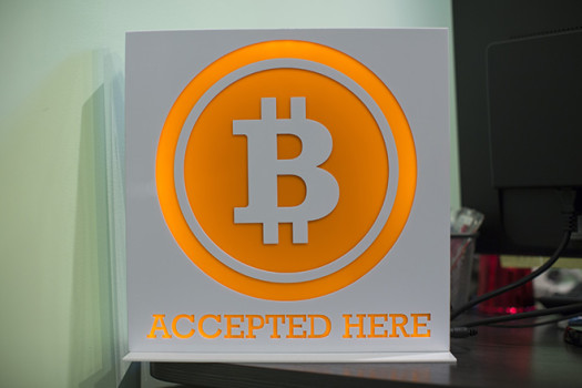 epa04122810 A Bitcoin sign is displayed in the lobby of the ANX office headquarters in Hong Kong, China, 13 March 2014. ANX, Hong Kong's largest Bitcoin exchange platform, is launching a Bitcoin auto teller machine (ATM) allowing people to buy the virtual currency without going online. EPA/JEROME FAVRE