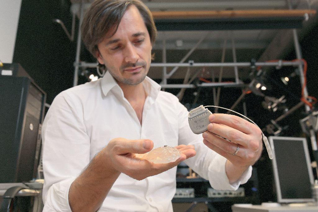 მეცნიერი გრეგორი კურტინი, რომელსაც ხელში მოწყობილობის მოდელი უჭირავს. ფოტო: (AFP Photo/)