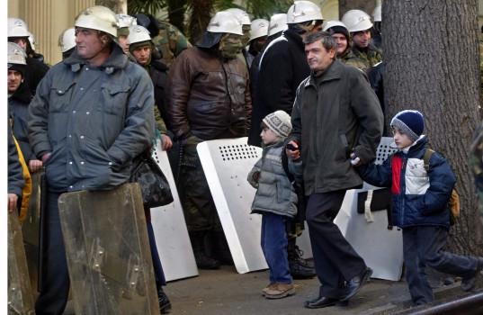 21 ნოემბერი. კაცი ბავშვთან ერთად კვეთს საქართველოს შინაგანი ჯარების კორდონს © EPA/SERGEI ILNITSKY