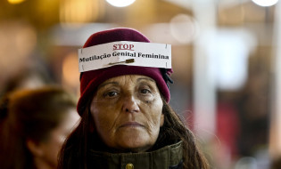 """ლისაბონში გენდერული ძალადობის წინააღმდეგ აქციის მონაწილე, წარწერით  – """"შეაჩერე ქალთა გენიტალიების დასახიჩრება"""". 25.11.2016. ფოტო:  EPA/MANUEL DE ALMEIDA"""