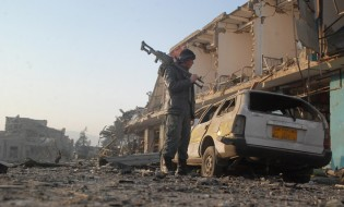 """ავღანელი ჯარისკაცი """"თალიბანის"""" თავდასხმის შედეგად დაზიანებულ საკონსულოსთან. 11.11.2016. ფოტო: EPA/MUTALIB SULTANI"""