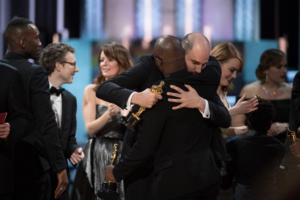 """""""მთვარის შუქზე"""" წლის საუკეთესო მხატვრულ ფილმას დაასახელეს, თუმცა მანამდე გაუგებრობის გამო ჯილდო """"ლა ლა ლენდს"""" გადასცეს. ფოტოზე """"ლა ლა ლენდის"""" პროდიუსერი ჯორდან ჰოროვიცი უბრუნებს ოსკარს ბარი ჯენკინსს. ფოტო: EPA/AARON POOLE"""