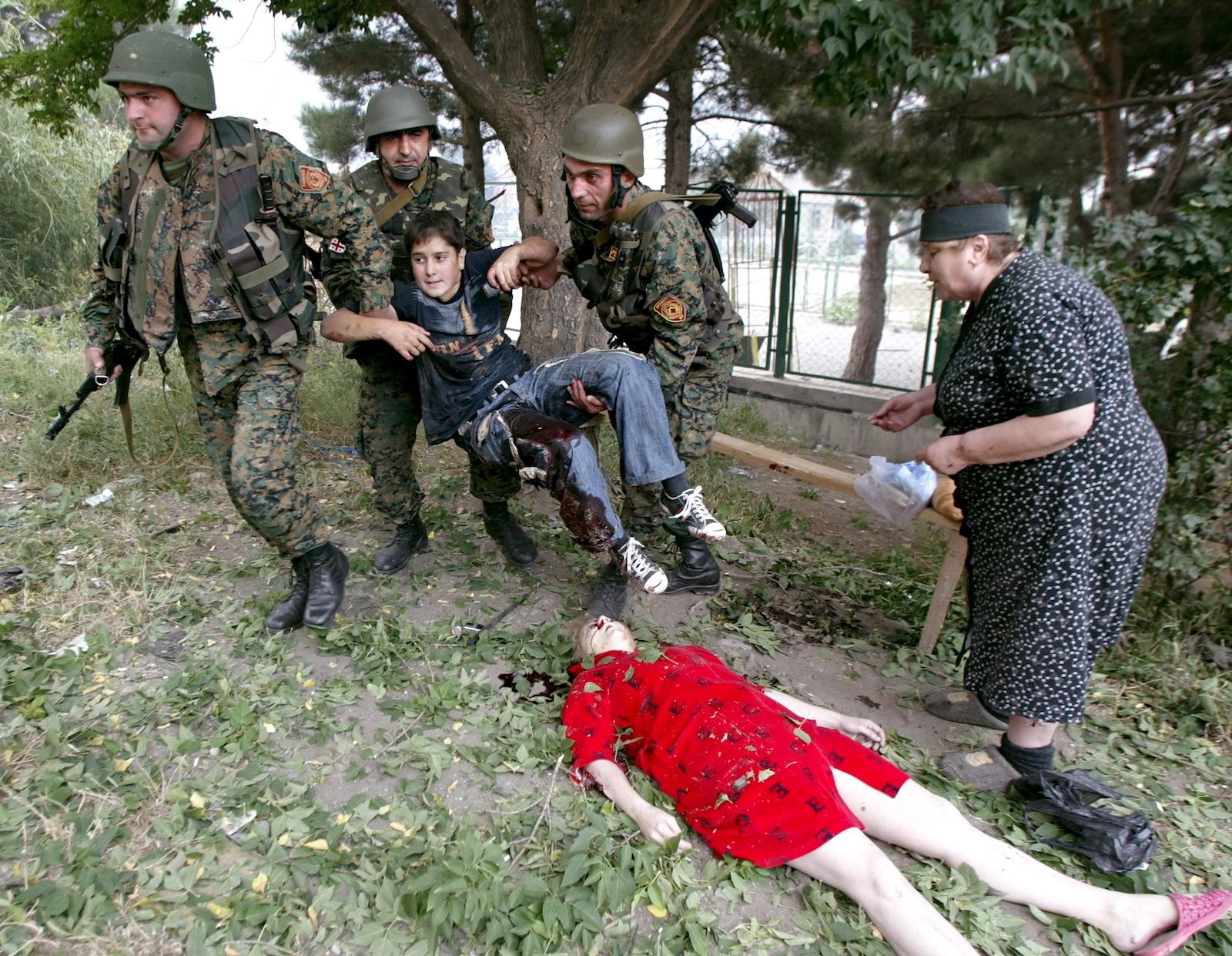 9 აგვისტო გორი. ჯარისკაცებს დაჭრილი ბავშვი მიჰყავთ. კადრში ასევე ჩანს საჰაერო შეტევის შედეგად გარდაცვლილი ბავშვი © EPA/ZURAB KURTSIKIDZE