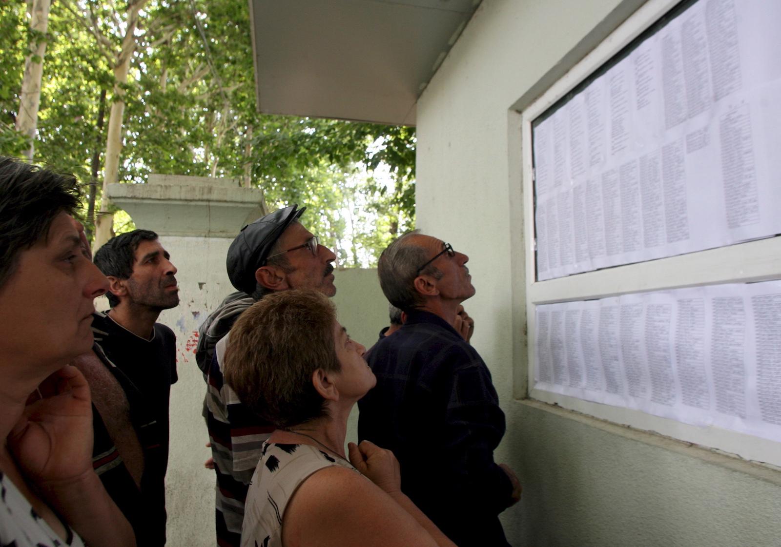 ქართველები გორში ამოწმებენ დაზარალებულებისა და გარდაცვლილების სიას 2008 © EPA/ZURAB KURTSIKIDZE