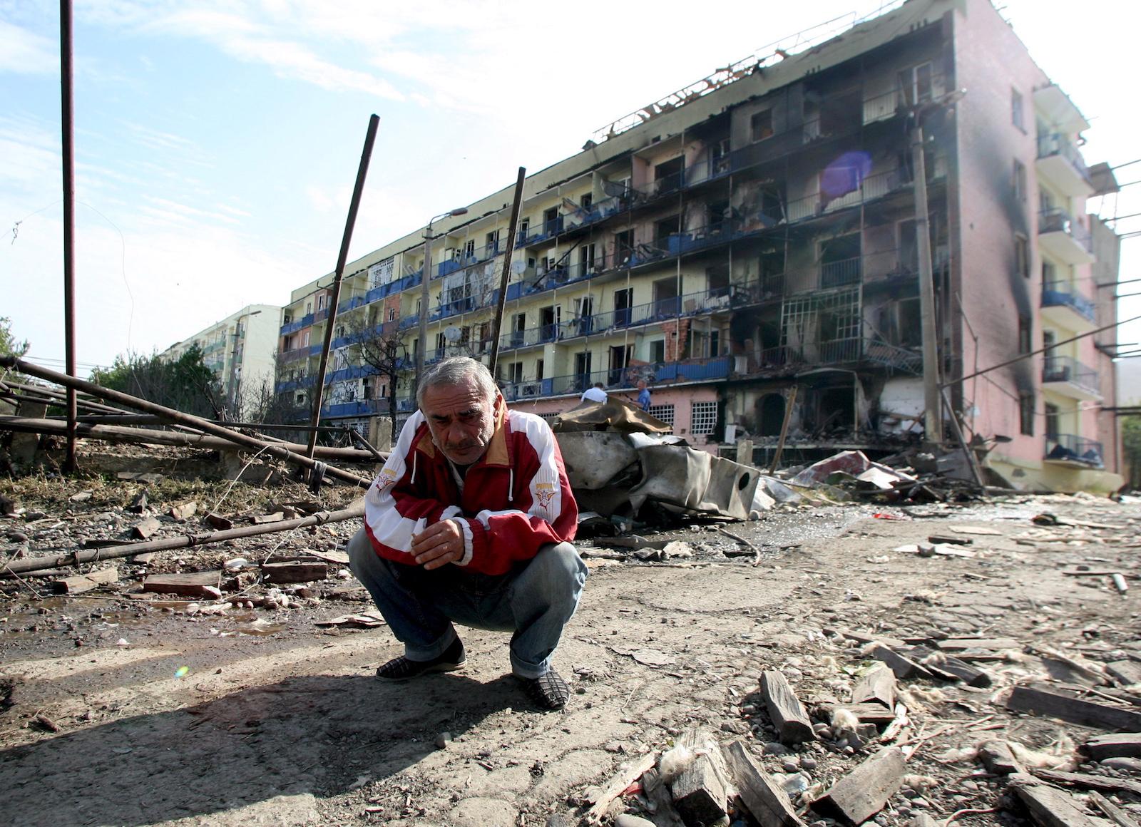 კადრში ჩანს გორელი კაცი. ფონზე დაბომბვის შედეგად დაზიანებული შენობა © EPA/ZURAB KURTSIKIDZE