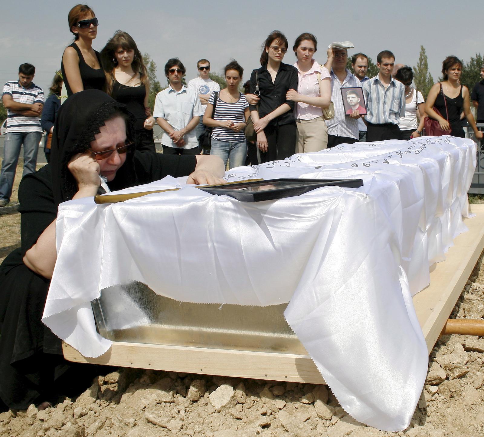 კადრში ხედავთ ფოტოჟურნალისტ ალექსანდრე კლიმჩუკის დედას შვილის დაკრძალვაზე. კლიმჩუკი მეორე ჟურნალისტ ჩიხლაძესთან ერთად კონფლიქტის ზონაში მოკლეს © EPA/VLADIMIR VALISHVILI