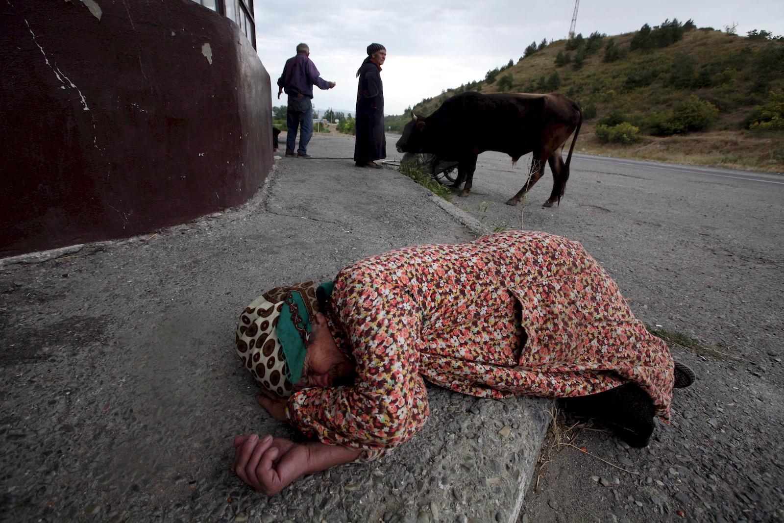 დევნილი, რომელმაც სოფელი კორთა დატოვა და 4 დღე ფეხით იარა გორთან ახლოს ისვენებს 15 © EPA/PAVEL WOLBERG