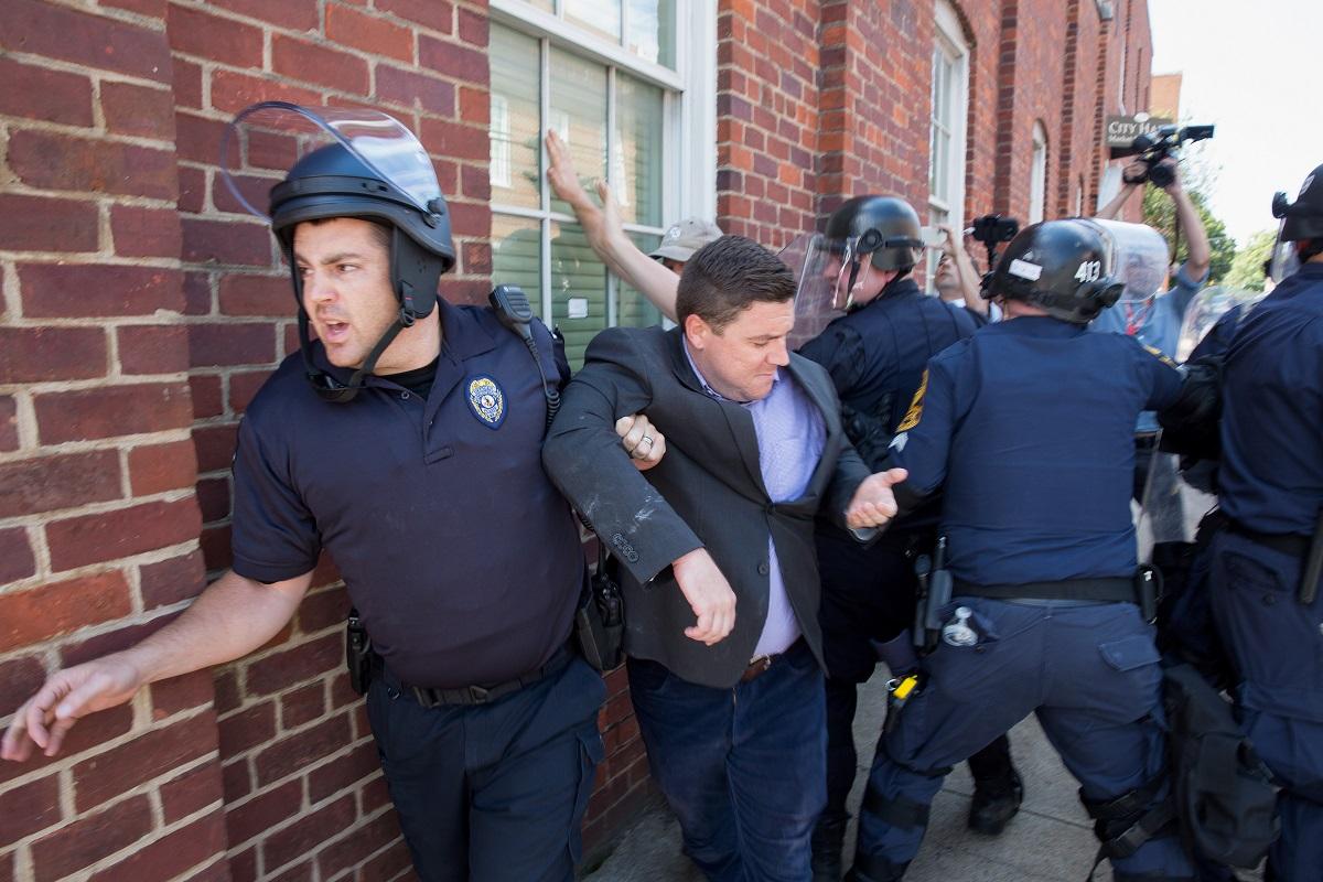 პოლიციას ქალაქის საბჭოს შენობიდან გაყავს ნაციონალისტური ჯგუფის წევრი, აქციის ორგანიზატორი ჯეისონ კელერი. ფოტო: EPA/TASOS KATOPODIS