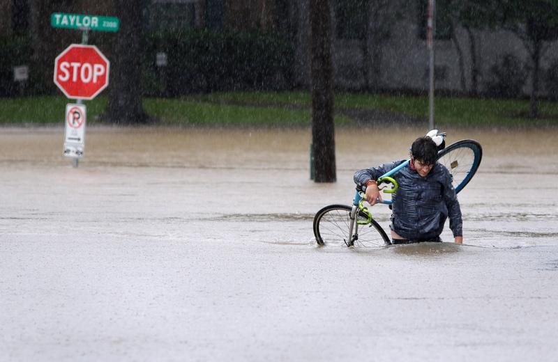 ახალგაზრდა კაცს დატბორილ ქუჩაში საკუთარი ველოსიპედი მიაქვს. ჰიუსტონი, ტეხასი. EPA-EFE/MICHAEL WYKE