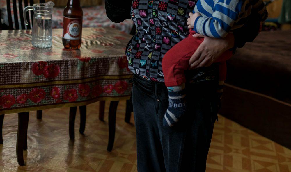"""ახალგაზრდა ქალი """"ვექტორის"""" დასახლებაში მცირეწლოვან შვილთან ერთად. ფოტო: ნეტგაზეთი/ქეთი მაჭავარიანი"""