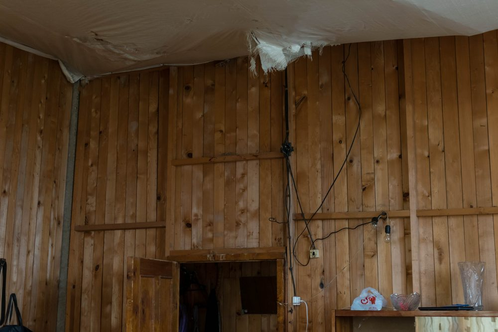 სანახევროდ ჩამონგრეული ჭერი და ხის კედელი, რომელიც დერეფნისგან ჰყოფს საცხოვრებელ ოთახს. როგორც ოთახის მეპატრონე გვეუბნება, ზამთარში ქარმა საერთოდ ჩამოანგრია ეს კედელი. ამ ოთახში დედა, მამა და სამი მცირეწლოვანი ბავშვი ცხოვრობს. ფოტო: ნეტგაზეთი/ქეთი მაჭავარიანი