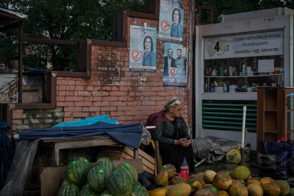 """ზუგდიდში ქალი ხილს ჰყიდის. მის უკან """"ევროპული საქართველოს"""" პლაკატებია გაკრული. ფოტო: ნეტგაზეთი/ქეთი მაჭავარიანი"""