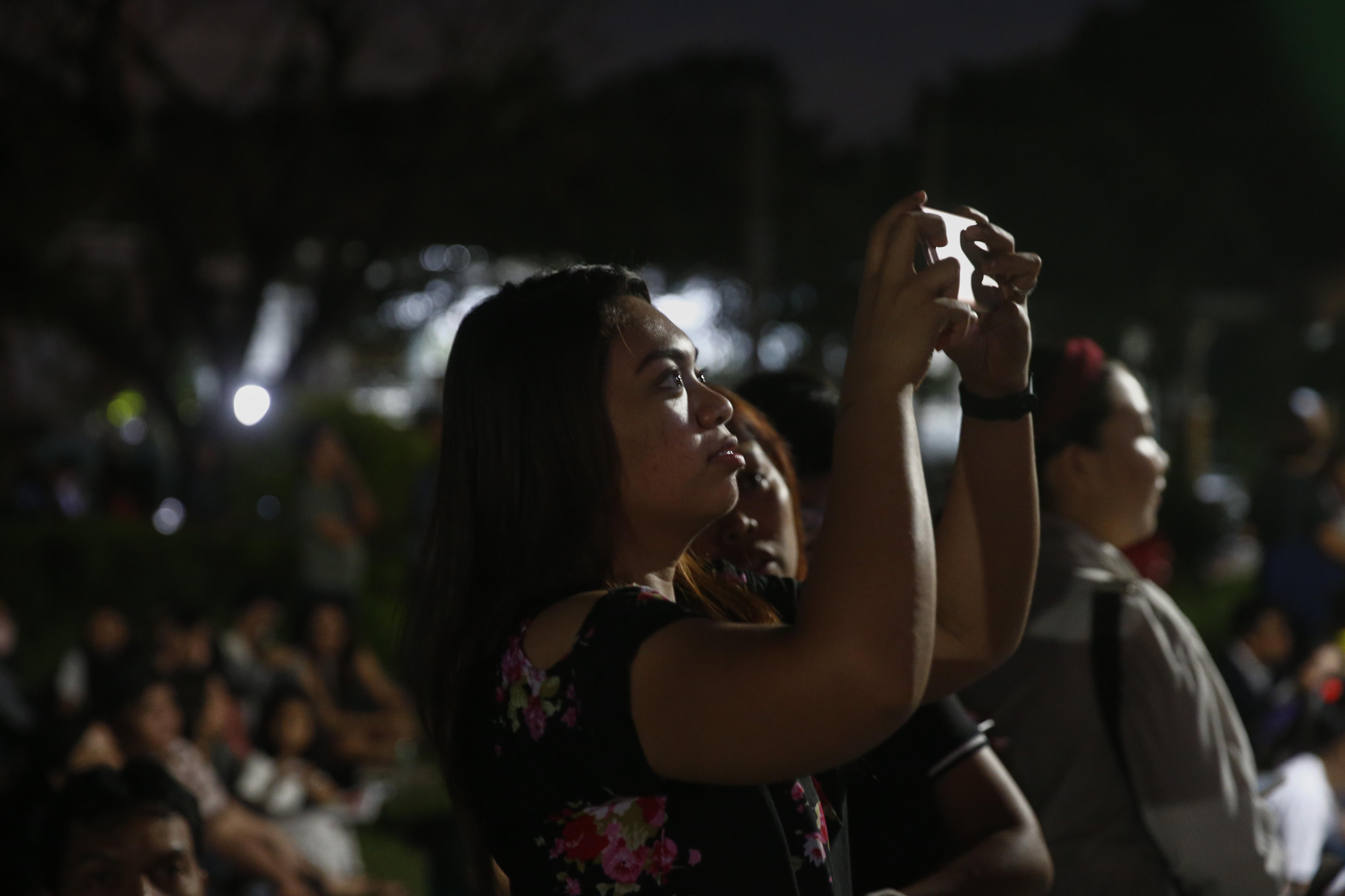 გოგონა იღებს სუპერმთვარეს ფილიპინების ქალაქ მანილაში. ფოტო: EPA/ROLEX-DELA-PENA
