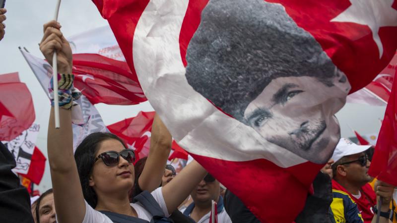 ქალი თურქეთის დროშითა და ათათურქის პორტრეტით წინასაარჩევნო შეხვედრაზე. ფოტო: EPA/SEDAT SUNA