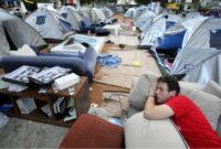 აქციის მონაწილეს სძინავს კარვების ქალაქში, თელ ავივში. ფოტო: EPAABIR SULTAN