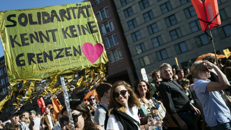 """აქციის მონაწილის პლაკატზე წერია: """"სოლიდარობამ საზღვრები არ იცის"""". ფოტო: EPA/აქცია ბერლინში. ფოტო: EPA/KAMIL ZIHNIOGLU"""