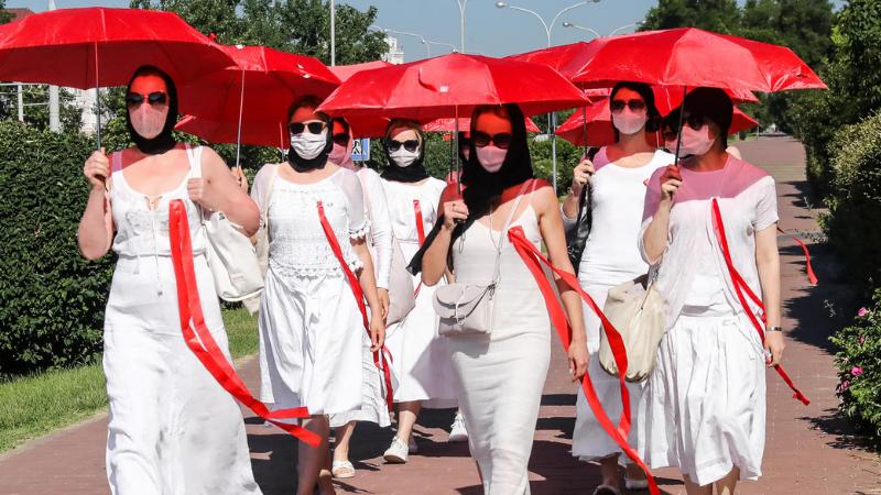მიუხედავად რისკებისა, ქალები მსვლელობას აწყობენ თეთრი კაბებითა და წითელი ქოლგებით —ბელარუსის პროტესტის სიმბოლოდ ქცეული დროშის ფერებით — მინსკში. 21.06.21 ფოტო: EPA